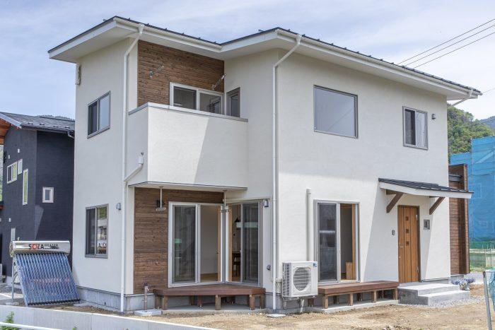 塗り壁と板張りの住宅外観の写真