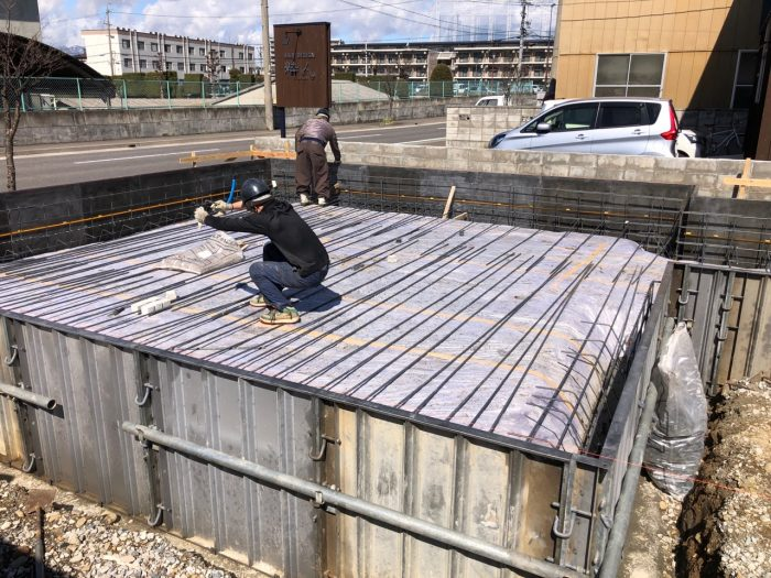 手作業で住宅用基礎の鉄筋をくみ上げる様子の写真